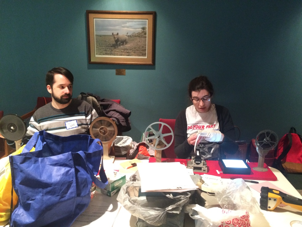Jake Riehl and Molly McBride, both 2nd year SLIS archives students, inspect film at the Home Movie Day event at the Brookfield Public Library. They're preparing 8mm and super8 film that patrons brought to the library to be projected. Many of the patrons had not been able to view their films for 20+ years!